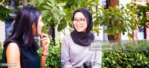 zwei muslimischen freundinnen unterhalten in kuala lumpur - zurückhaltende kleidung stock-fotos und bilder