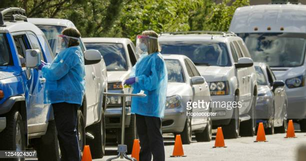 two female nurses wearing gowns, surgical face masks, gloves, and face shields talk to patients in their cars in a drive-up (drive through) covid-19 (coronavirus) testing line outside a medical clinic/hospital outdoors (second wave) - drive through stock pictures, royalty-free photos & images