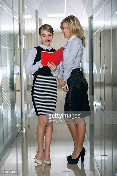 Two female office workers discussing issues