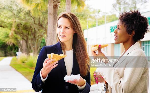 Two female office workers enjoying pizza outdoors lunch break