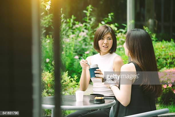 Two female office workers having lunch together outdoor