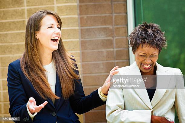 Two female office workers laugh at irresistible joke outdoors
