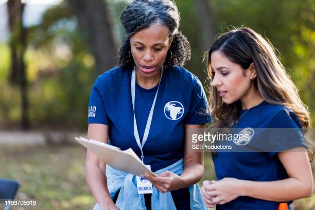 two female park cleanup volunteers review registration lists - community logo stock pictures, royalty-free photos & images