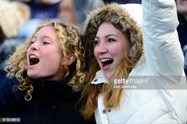 Two female Penn State fans in the student section wear winter clothes winter coats and yell cheer and sing in the stands The Penn State Nittany Lions...