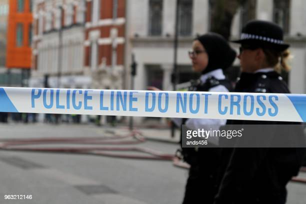 two female police officers standing behind  police do not cross tape - cordon boundary stock pictures, royalty-free photos & images