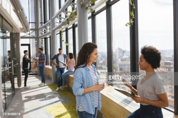 twee vrouwelijke programmeurs die een digitale tablet samen in een bureaugang gebruiken - incidental people stockfoto's en -beelden
