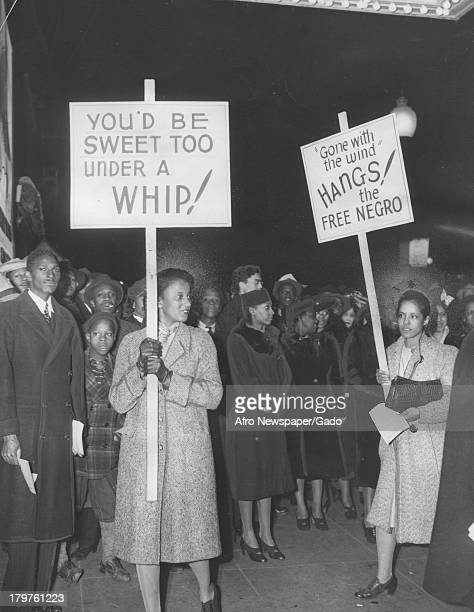 Two female protesters are shown holding signs marching for civil rights and protesting a play depicting 'Gone With The Wind' March 9 1940