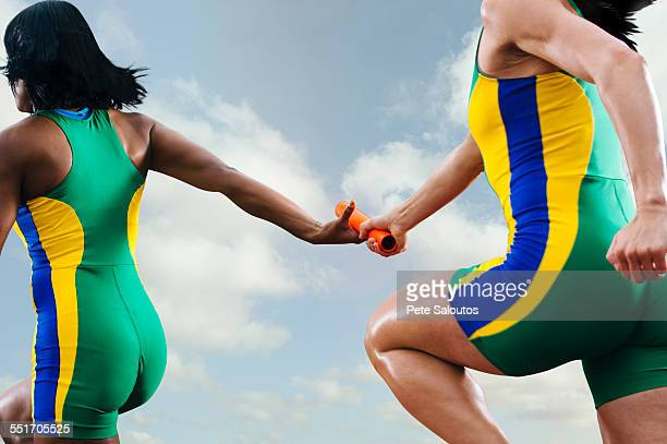 two female relay athletes exchanging baton whilst running - sports team event fotografías e imágenes de stock