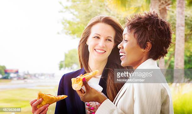 Two female reps laugh while eating pizza outdoors during event