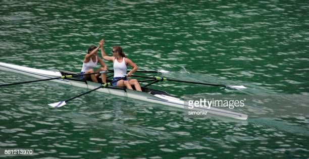Two female rowing athletes doing high five on double scull