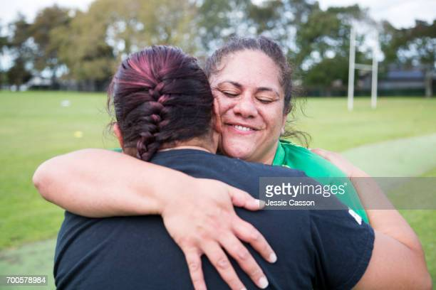 two female rugby players hugging on rugby field - reportage stock pictures, royalty-free photos & images