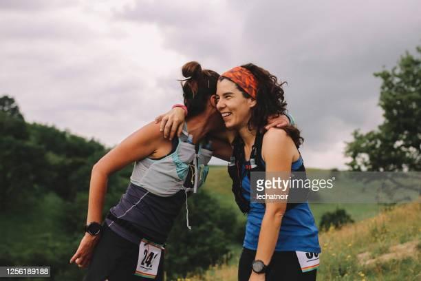 2人の女性ランナーが自然の中で祝う - ハーフマラソン ストックフォトと画像