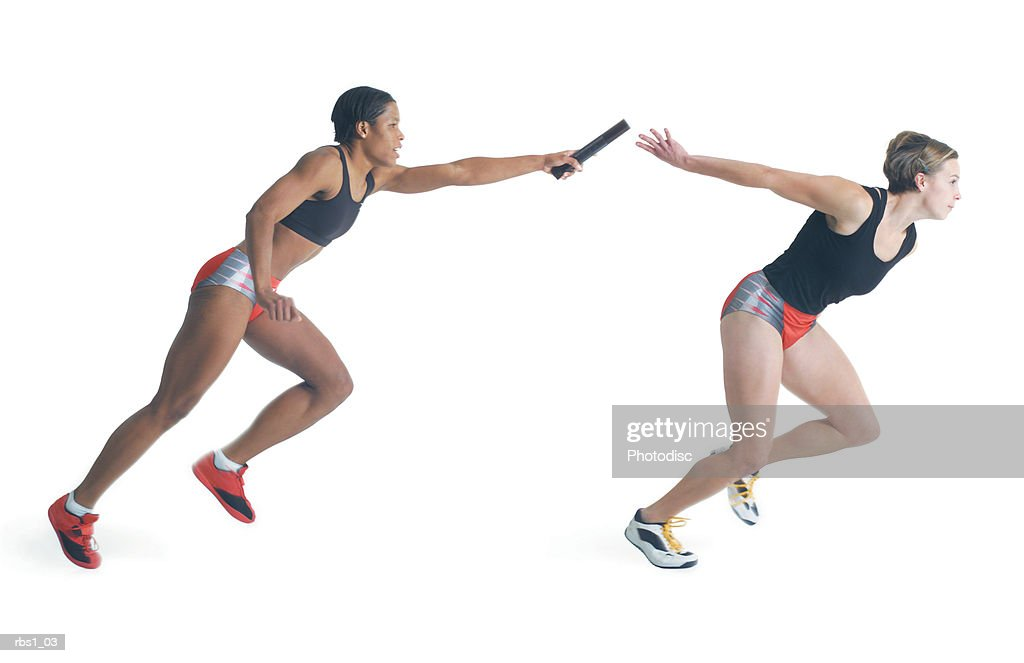 two female runners wearing black red and silver pass a baton as they run a race : Foto de stock
