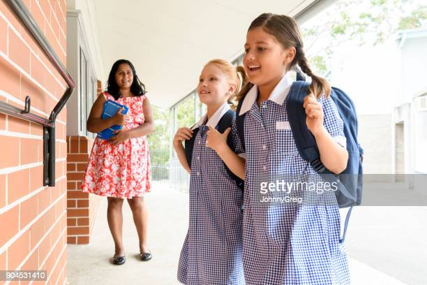 Two female school friends with backpacks and teacher in background