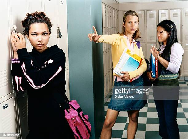 two female secondary school students making rejection gestures towards a goth girl - young goth girls stock pictures, royalty-free photos & images