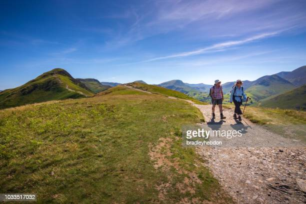 Two female senior hikers descend Cat Bells fell in Keswick, England