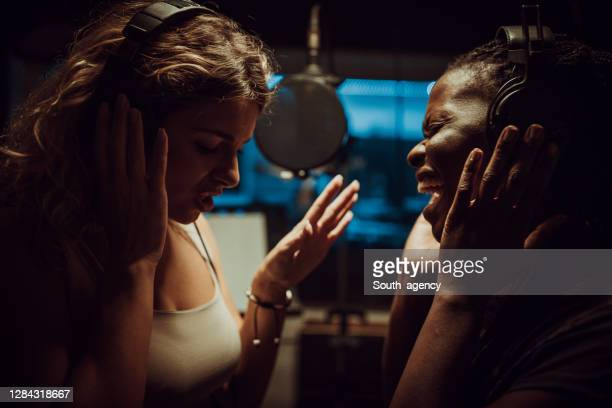 two female singers recording a song in the professional studio - singer stock pictures, royalty-free photos & images