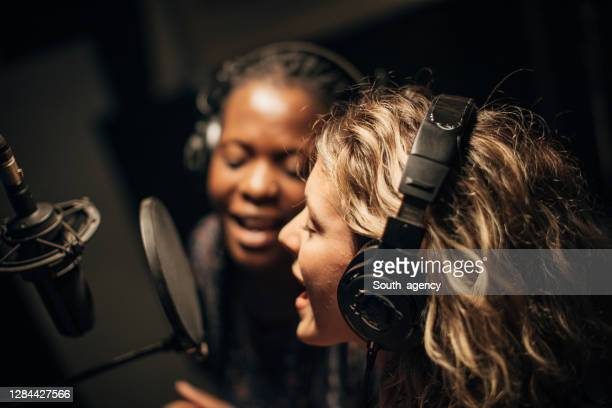 two female singers singing a duet in recording studio together - recording studio stock pictures, royalty-free photos & images