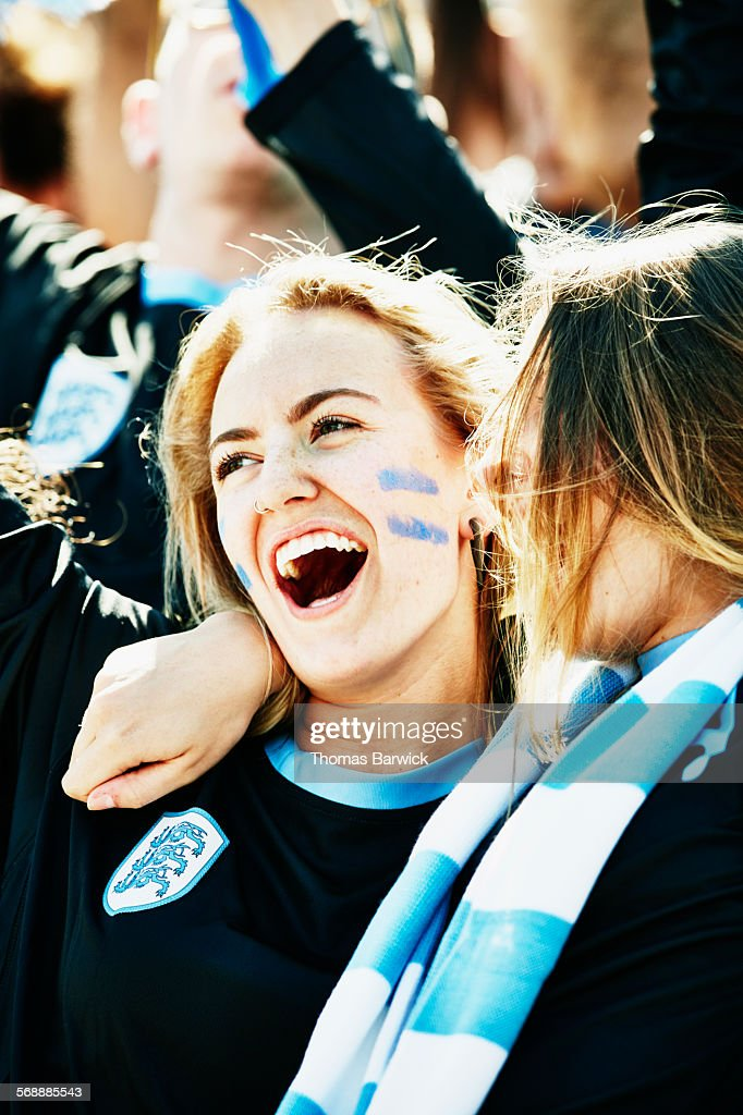 Two female soccer fans in crowd celebrating goal : Stock Photo