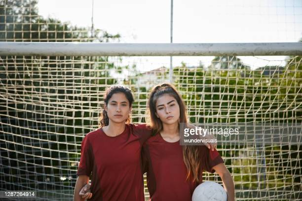 two female soccer players looking at camera by soccer net - club football stock pictures, royalty-free photos & images