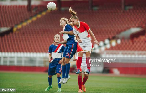 Two female soccer rivals heading the ball on a match.