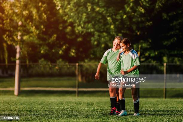 two female soccer teammates celebrating after scoring a goal