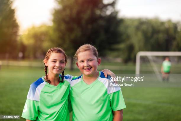 two female soccer teammates with their arms around each other on soccer field - calcio di squadra foto e immagini stock