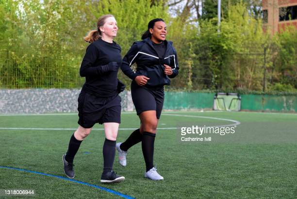 two female soccor players warming up on soccer pitch - menopossibilities stock pictures, royalty-free photos & images