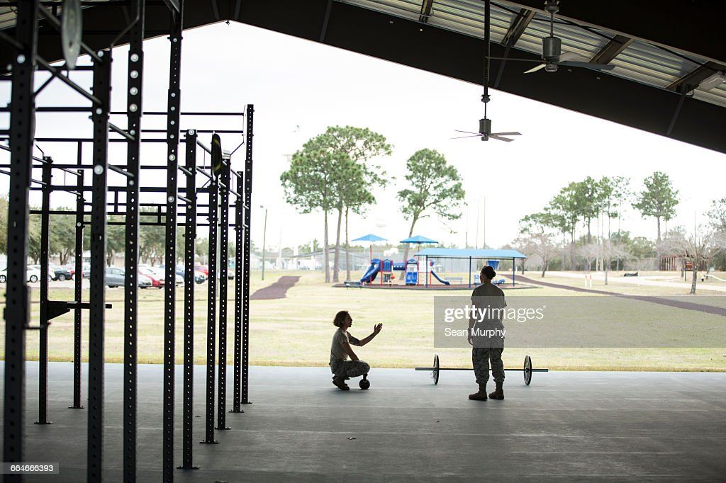 Two female soldiers barbell training at military air force base : Stock Photo