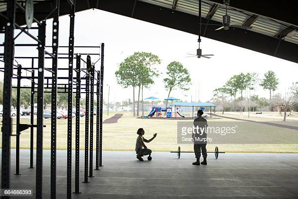 Two female soldiers barbell training at military air force base