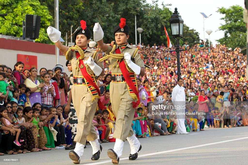 Two female soldiers marching at the closing of the (India/Pakistan) `Ceremony` Border at Wagah, from the Indian side, Punjab, India