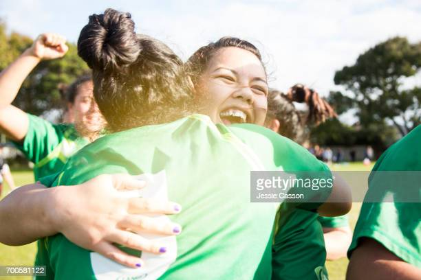 Two female sports players have celebratory embrace on field