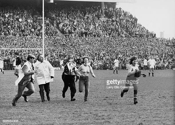 Two female streakers run across the pitch at Twickenham Stadium in London during the England v Scotland Calcutta Cup March 1983