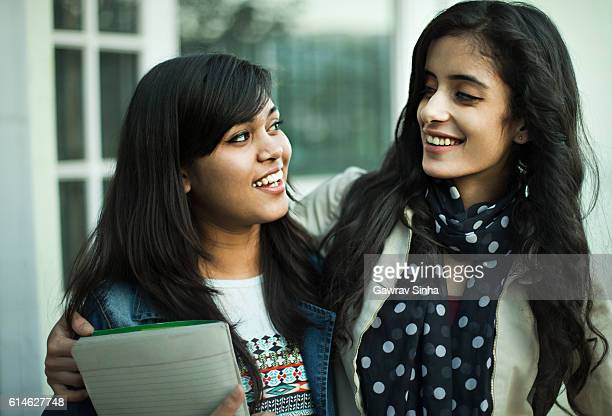 Two female student friends with arm around shoulders standing together.