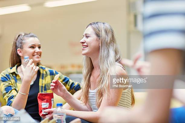 Two female students eating crisps in canteen at higher education college