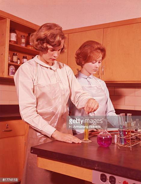 two female students in chemistry laboratory, conducting experiment. - 1960 stock pictures, royalty-free photos & images