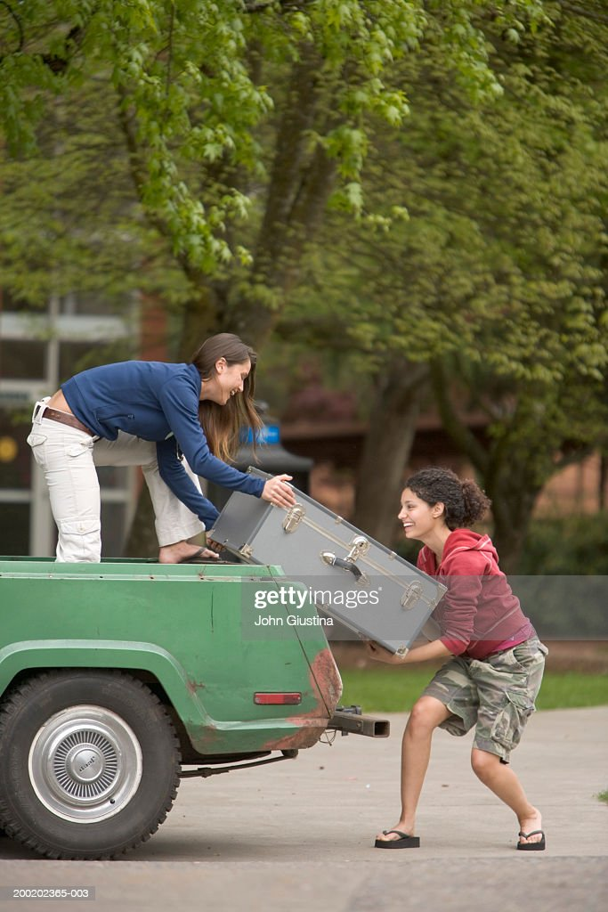 Two female students lifting trunk onto truck, side view : Foto de stock