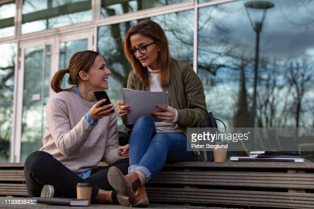 Two female students looking at phone