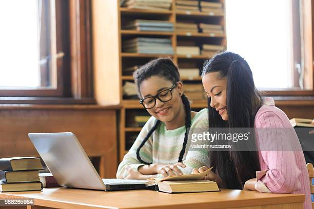 Two female students studying together in the library