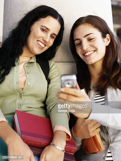 Two female students using mobile phone, smiling