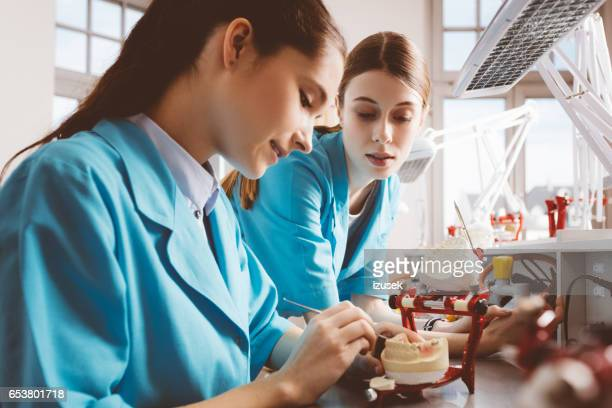 Two female students working on denture