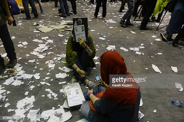 Two female supporters of Hassan Rouhani, one of the eight candidates approved to run for the Iranian presidency seen sat on the ground amid torn...