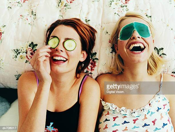 two female teenagers lying in bed wearing eye masks - cosmetics stock pictures, royalty-free photos & images