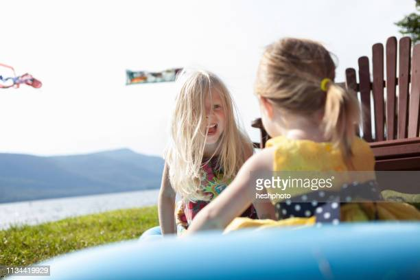 two female toddlers sitting on air bed, silver bay, new york, usa - heshphoto stock pictures, royalty-free photos & images