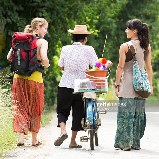 two female tourists and local farmer walking down country road, chiang mai, thailand - hugh sitton stock pictures, royalty-free photos & images
