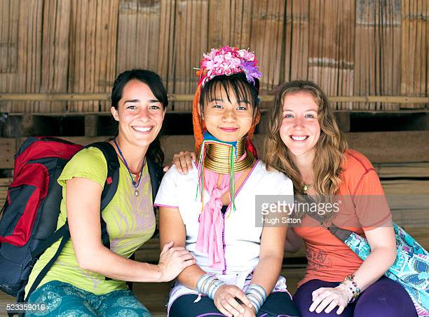 two female tourists and local traditionally-dressed woman, chiang mai, thailand - hugh sitton stock pictures, royalty-free photos & images