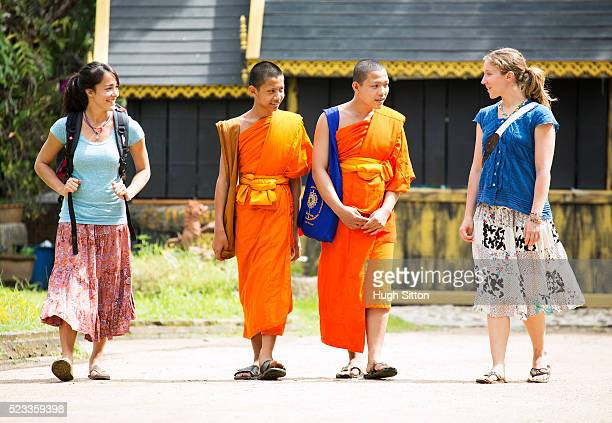 two female tourists and two local monks chatting, chiang mai, thailand - hugh sitton foto e immagini stock