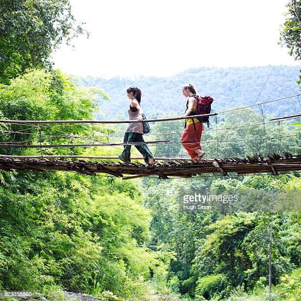 two female tourists crossing hanging bridge - hugh sitton - fotografias e filmes do acervo