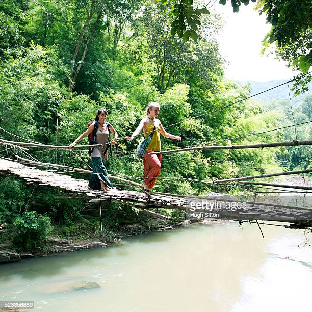 two female tourists crossing hanging bridge - hugh sitton stock-fotos und bilder
