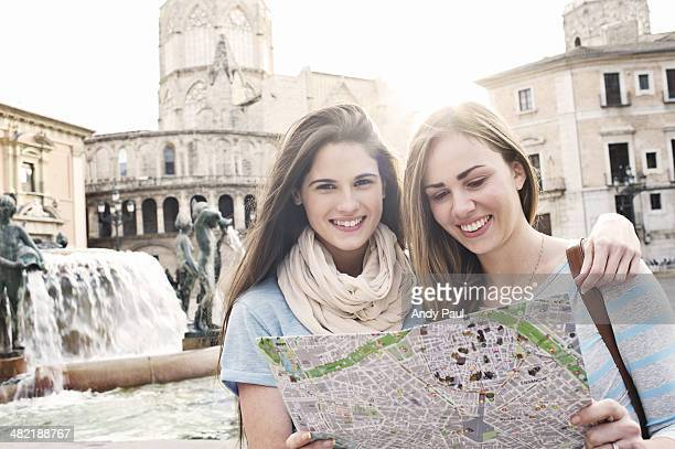 Two female tourists looking at map, Plaza de la Virgen, Valencia, Spain